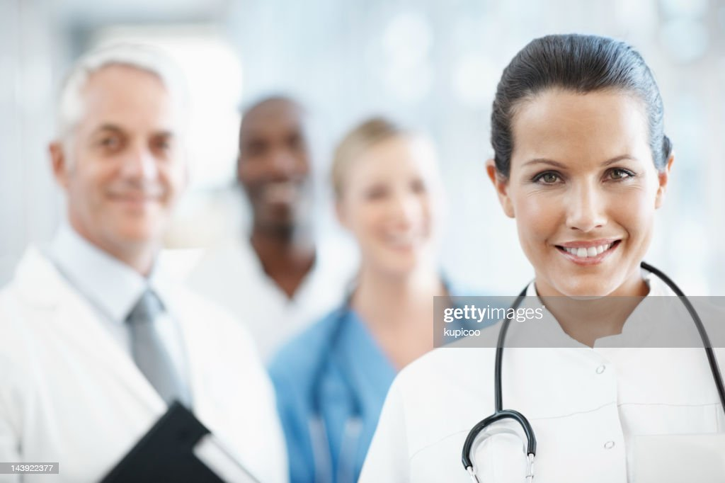 Beautiful female doctor with medical team in background : Stock Photo