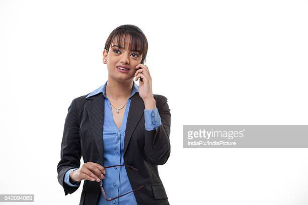 Beautiful female executive on call over white background