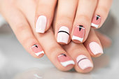 Beautiful female hands with a fashionable manicure. Geometric design of nails. Photo closeup