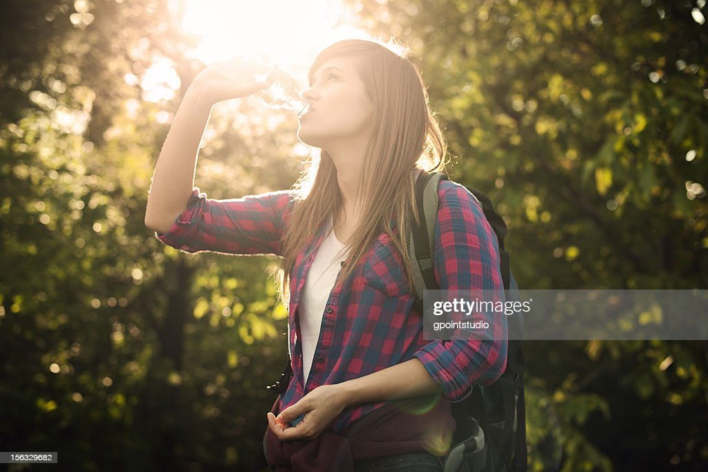 Beautiful female hiker drinking water in forest at sunset