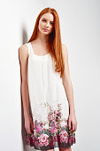 Tender portrait of beautiful redhead female wearing sleeveless flower print summer dress posing leaning against white wall