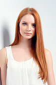 Tender portrait of beautiful redhead female posing leaning against white wall