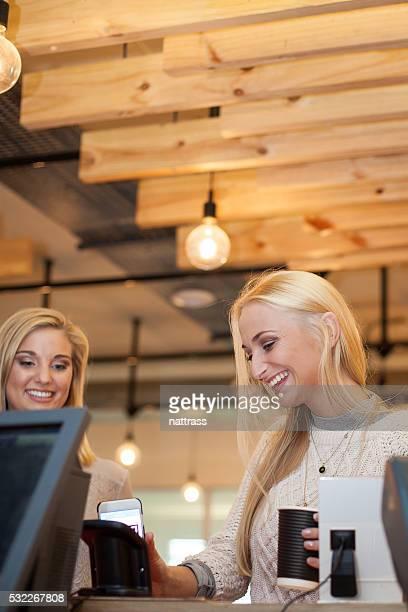 Belle femme est tellement enthousiaste à payer avec son smartphone