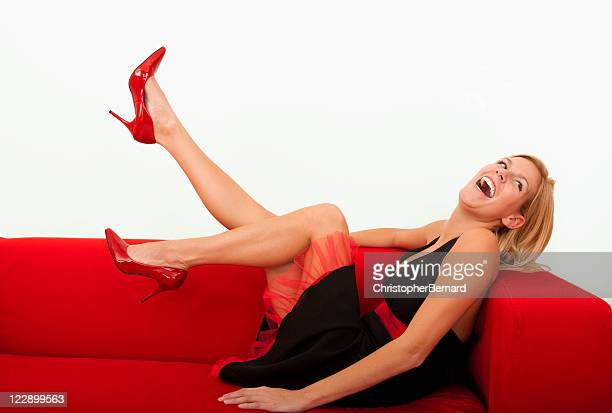 Beautiful female laughing on a red sofa