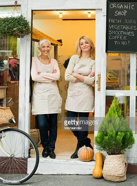 Belle femme propriétaire tenant debout en face de la boutique