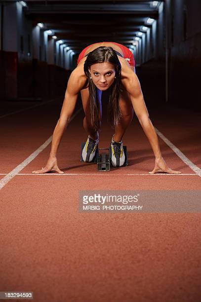 Beautiful female sprinter on starting blocks