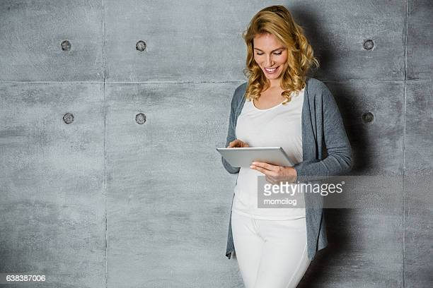 Beautiful female standing with tablet and smiling