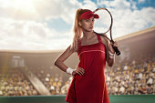 beautiful female tennis player in pink tennis apparel on court with a racket