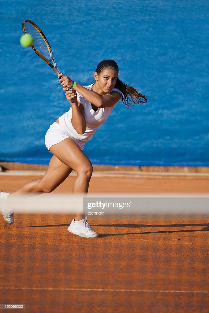 Beautiful female tennis player on the blue background