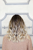 Beautiful woman with balayage hairstyle back view. Lovely modern and fashion hairstyles. Curly short or long hair. Space for text
