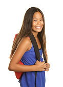 A cute eleven year old Filipino girl with a backpack on a white background.  She is looking at the camera with a big smile.