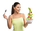Beautiful, fit young woman holding a bowl of salad