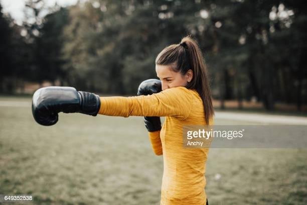 Schöne Fitness-Frau-Boxen mit schwarzen Handschuhen