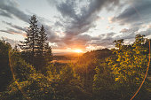 The sun goes down between clouds and an expansive view of trees in a valley.