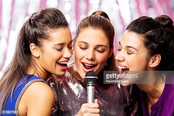 Wunderschöne Freunde mit Mikrofon singen Karaoke im Nightclub