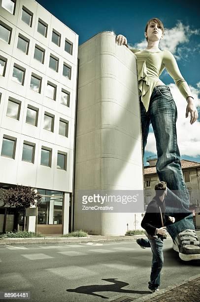 Beautiful giant girl pursuit man in urban scenery