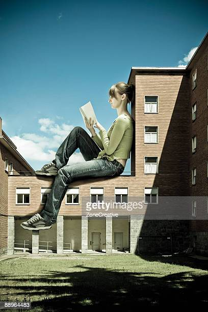 Beautiful giant girl rread book over school buildi
