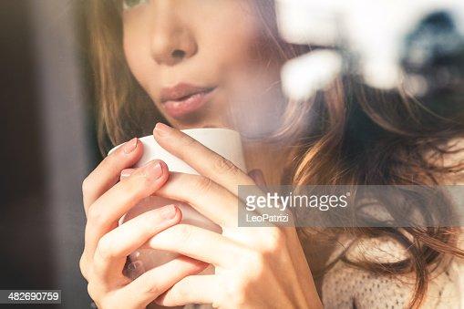 Beautiful girl blowing on coffee cup