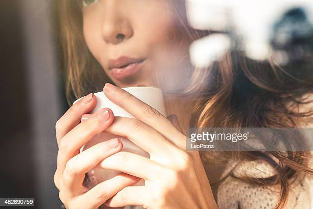 Beautiful girl blowing on coffee cup
