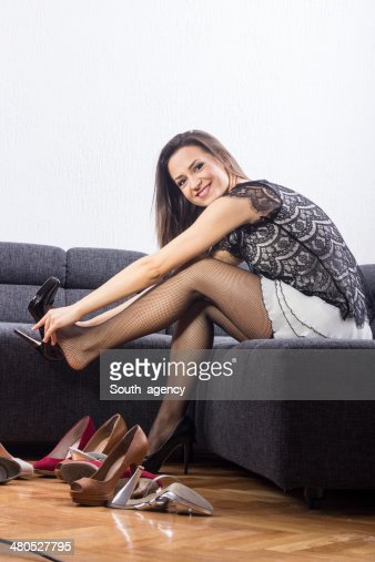 Beautiful girl chooses shoes in room : Stockfoto