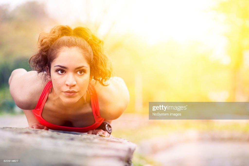 Beautiful girl doing push ups outdoor