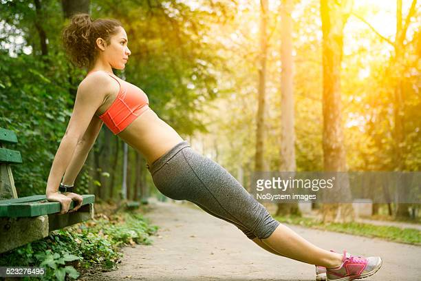 Beautiful girl doing push ups outdoor