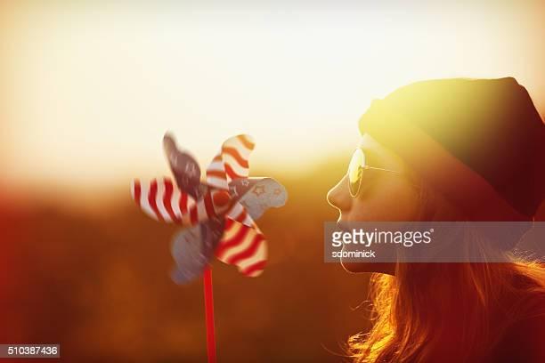 Belle fille avec moulin à vent au coucher du soleil