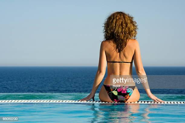 Bella ragazza godendo la vista della piscina a straripamento