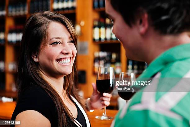 Beautiful girl  gives her boyfriend a wide smile in bar