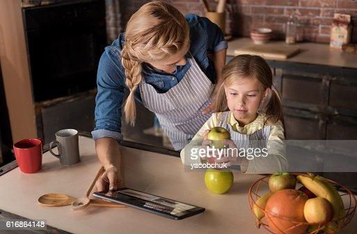 Beautiful girl having fun with her mother in the kitchen : Stock Photo