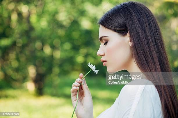 Schönes Mädchen hält eine Blume in der hand
