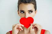 Studio shot of young beautiful woman holding artificial heart. Professional make-up.
