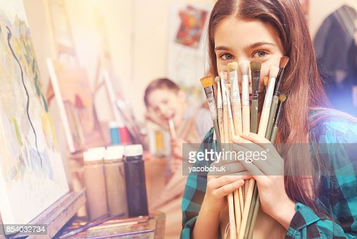 Beautiful girl holding bunch of messy painting brushes : Stock Photo