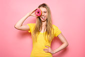 Beautiful girl holding donut an having fun isolated on pink background. People with sweets.