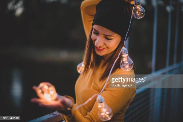 Beautiful girl holding light bulbs