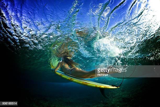 Beautiful girl in a bikini duckdives a wave
