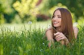Beautiful young woman enjoying nature in the open air,lying on green grass in the Park.Happy and Healthy Smiling brunette Girl with healthy smile relaxing in the Summer Park. Breathing fresh air. Sunn