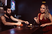 A beautiful girl in a red dress is holding a straw and waiting for the barman to make a cocktail at the bar.