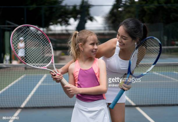 Beautiful girl in a tennis class with her teacher