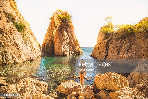 Beautiful girl in bikini posing in a stunning hidden beach between ...