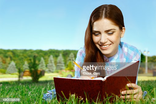 Beautiful girl in park with her diary : Stock Photo