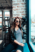 Beautiful girl in sunglasses posing on camera near window