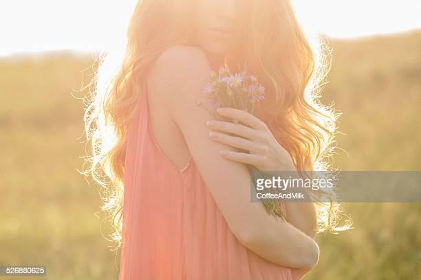 Schöne Mädchen in den Strahlen der Sonnenuntergang