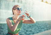 Beautiful young girl with pink hair in vintage clothing blowing bubbles outdoor