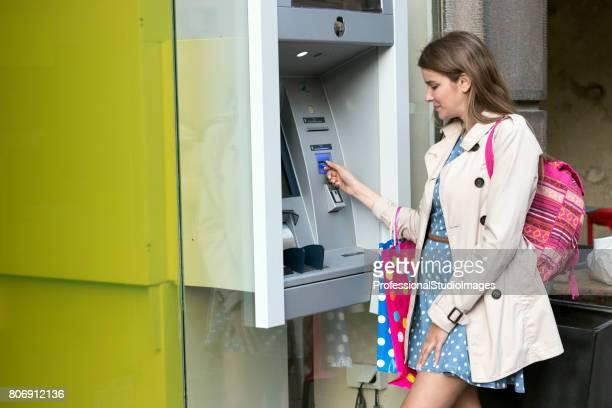 Belle fille, insertion d'une carte de crédit au guichet automatique