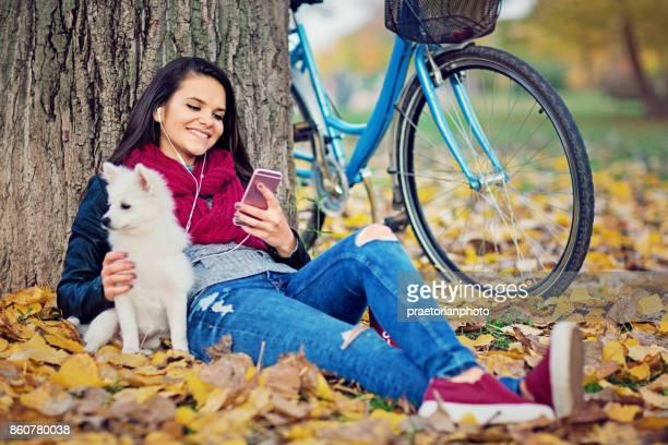 Schönes Mädchen sitzt auf dem Herbstlaub und hören die Musik mit ihren kleinen Hund