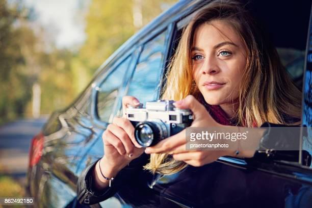 Mooi meisje is fotograferen met een vintage camera vanuit de auto