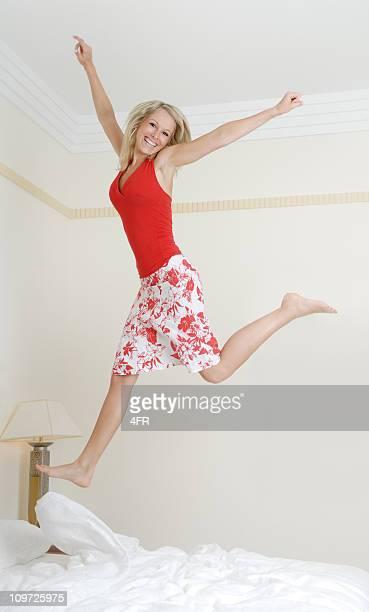 美しい女の子をジャンプのベッド