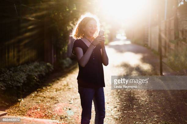 A beautiful girl looking at her cellphone in an alley at sunset