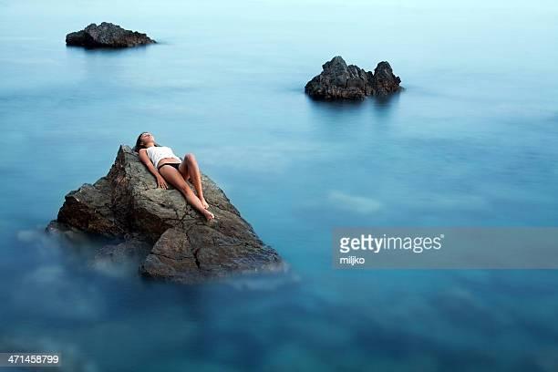 Beautiful girl lying on rock in the sea.
